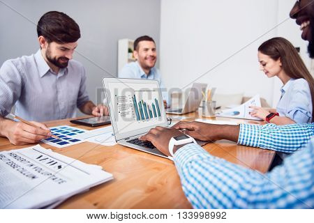 Working day. Positive concentrated colleagues sitting at the table and working while expressing gladness