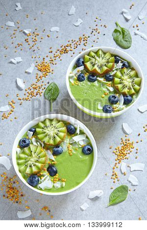 breakfast green smoothie bowl topped with kiwi, blueberry, coconutflake and bee pollen