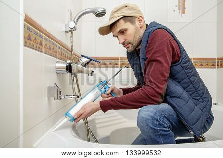 Plumber caulking bathtub with silicone glue using caulking gun.