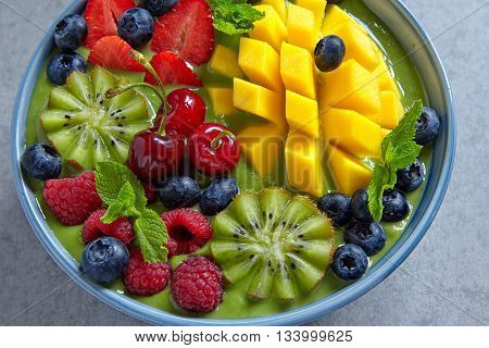 breakfast green smoothie bowl topped with fruits and berries