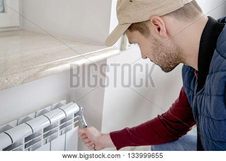 Male plumber repairing radiator with wrench. Worker looking at the radiator. Close-up.