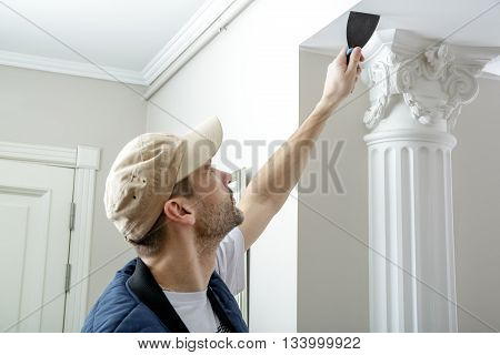 Male holds putty knife on the wall near the wall corner. Finishing work.
