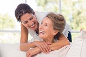 Portrait of mother and daughter hugging. Happy senior mother and adult daughter embracing at home. C poster