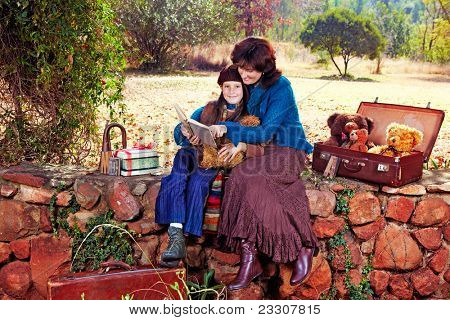mother and daughter reading vintage books sitting on the wall in the garden with bears on a sunny autumn day.