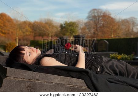 Beautiful dead woman lying in gothic dress on a tomb