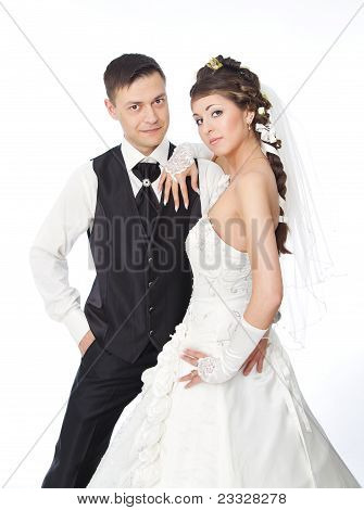 Beautiful Bride And Groom Standing At White Background. Wedding Couple Fashion Shoot.