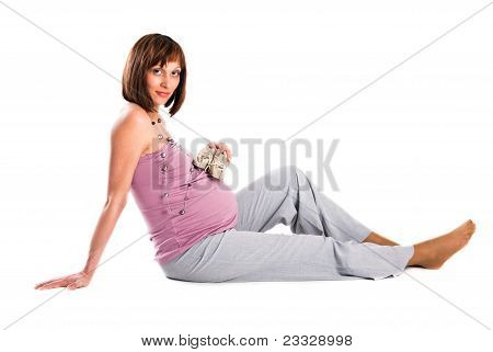The Pregnant Woman Sits On A Floor, A White Background..