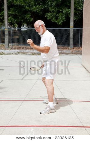 Fit senior man playing racquetball on a public court.