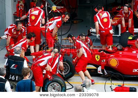 SEPANG, MALAYSIA - APRIL 8: Scuderia Ferrari F1 Team pit crew practice tire change in the pit-lane on the first practice day of the Petronas Malaysian F1 Grand Prix on April 8, 2011 Sepang, Malaysia.