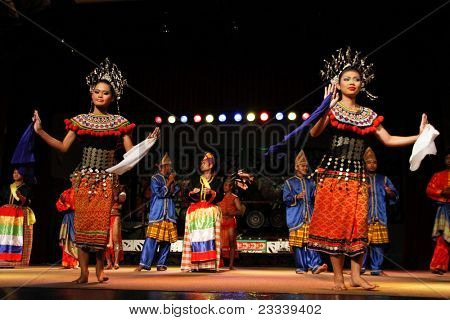 KUCHING, BORNEO ISLAND - MAY 14: Dancers from the indigenous Iban people dance on stage to welcome guest at the Sarawak Cultural Village on May14, 2010 in Kuching, Borneo Island.