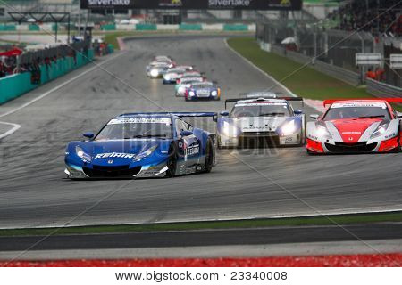 SEPANG - JUNE 19: Cars take off from a rolling start at the Japan SUPER GT Round 3 race at the Sepang International Circuit on June 19, 2011 in Sepang, Malaysia. The GT500 cars start in the front.