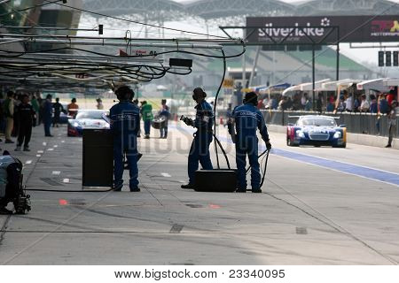 SEPANG - JUNE 19: Team Impul's pit-crew waits for their car to come in during the practice round of the Japan SUPER GT Round 3 race on June 19, 2011 in Sepang international Circuit, Malaysia.