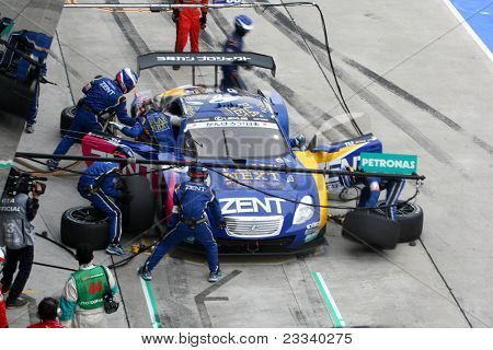 SEPANG - JUNE 19: Lexus Team Zent Cerumo's pit crew prepares to refuel and change tires during a pit-stop of the Japan SUPER GT Round 3 race on June 19, 2011 in Sepang International Circuit, Malaysia.