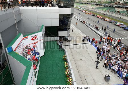 SEPANG, MALAYSIA - JUNE 19: Winners of the GT500 SUPER GT race pose on the podium and celebrate with team and fans at the Sepang International Circuit on June 19, 2011 in Sepang, Malaysia.