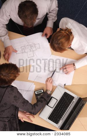 Three Architects Working With Blueprints