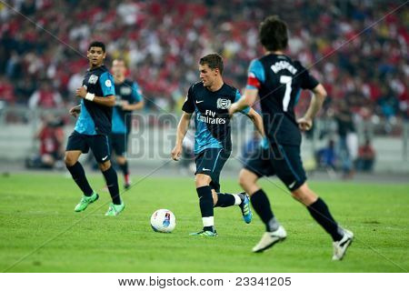 BUKIT JALIL, MALAYSIA - JULY 13: Arsenal's Aaron Ramsey (blue boots) leads an attack against Malaysia on July 13, 2011 in Stadium Bukit Jalil, Malaysia. English league team Arsenal is on an Asia Tour.