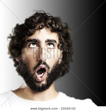 young man imitating a zombie against a black background