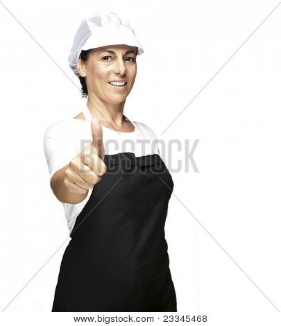 portrait of cook wearing apron and mesh top hat doing okey symbol against white background