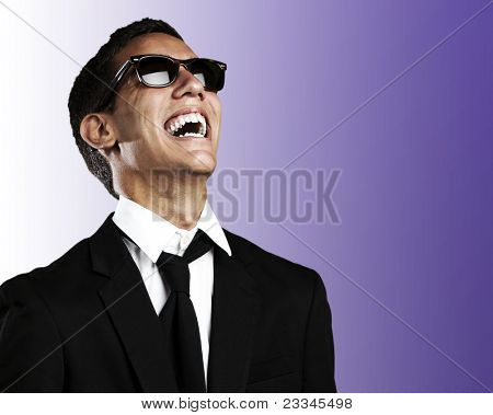 portrait of young business man with suit and sunglasses laughing against a purple background
