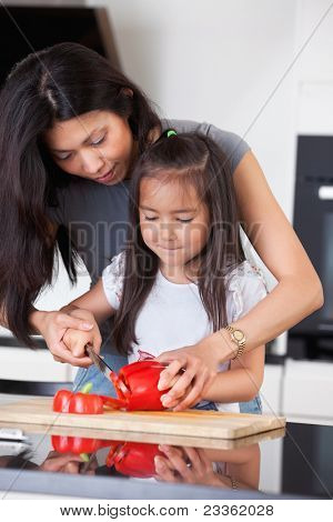 Little girl cutting pepper with the help of her mother