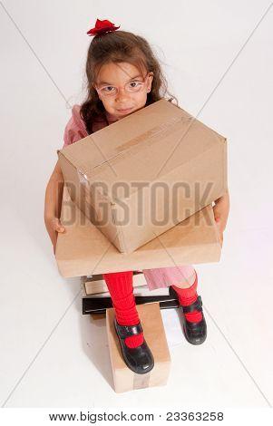 Uma garotinha sentado sobre uma pilha de livros, segurando grandes caixas de papelão