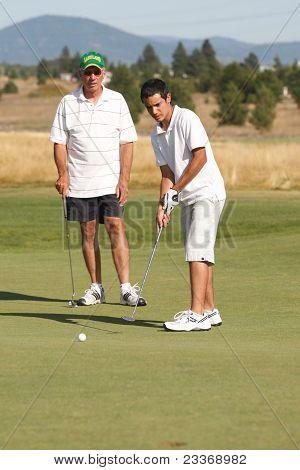 Adolescente golfista Putts la bola.