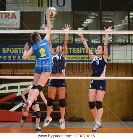 KAPOSVAR, HUNGARY - APRIL 24: Zsanett Pinter (blue 2) in action at the Hungarian NB I. League woman volleyball game Kaposvar (blue) vs Ujbuda (black), April 24, 2011 in Kaposvar, Hungary.