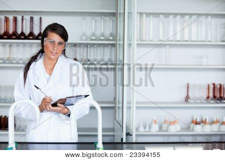 Cute Female Scientist Writing On A Clipboard