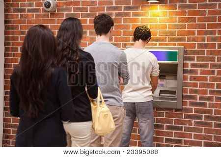 Young People Queuing To Withdraw Cash