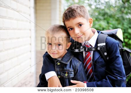 First-grader boy hugs his younger brother