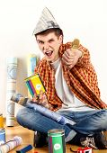 Repair home man holding paint roller for wallpaper. Tired and frustrated mad male in newspaper cap r poster