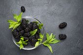 Glass Plate With Ripe Blackberries And Green Mint Leaves On A Black Surface. Macro Photo Of Ripe Bla poster