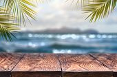 Beach blurred background with palm leaves background with vintage old wood table poster