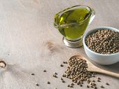 Hemp Seeds And Hemp Oil On Brown Wooden Table. Hemp Seeds In Wooden Spoon, In Small Bowl And Hemp Oi poster