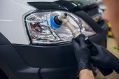 Постер, плакат: Auto Mechanic Buffing And Polishing Car Headlight Car Detailing Man With Orbital Polisher In Auto