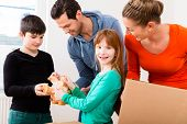 Family moving into new home carrying packing cases poster