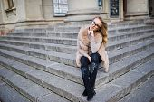 Blonde Girl At Fur Coat And Glasses Sitting On Stairs. poster