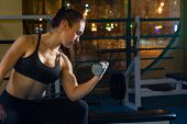 Woman Lifting Dumbbells In The Gym On Background Of Night Town. Weightlifting In Sports Club, Keep H poster