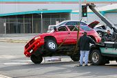 image of wrecker  - a red sport utility was hit and rolled over by the blue car behind it - JPG