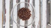 Coffee Beans Heap In Glass Heap On Wooden Table, Top View poster