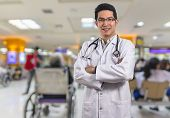 Portrait Of Asian Doctor With The Stethoscope Equipment Over Abstract Photo Blurred Of Hospital Back poster