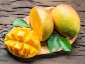 Mango fruits and mango slices on the old wooden table. Organic food. poster
