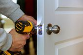 Carpenter Install Door Lock Using Screwdriver At Home Installation Of Locks On The Door poster