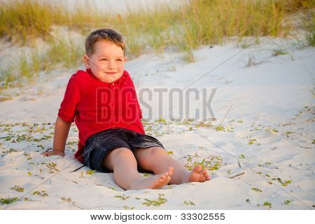 Retrato de criança feliz na praia com dunas de areia no fundo