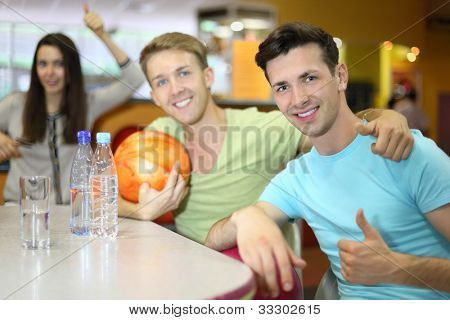 Two men and woman with balls sit at table in bowling and thumb up; bottles and glass with water on table; focus on right man; shallow depth of field