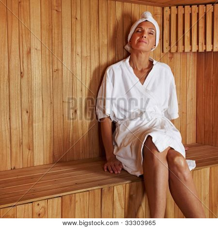 Senior woman sitting relaxed in a wooden sauna