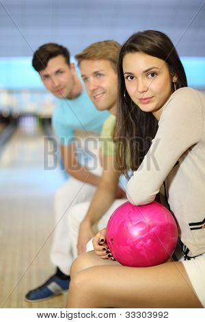Two happy men and woman sit in bowling club; girl holds pink ball; focus on woman; shallow depth of field