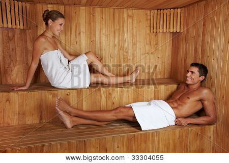Attractive man and young woman talking to each other in sauna