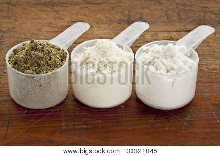 plastic measuring sccps of three protein powders (from left hemp seed, whey concentrate, whey isolate) on a grunge wood surface