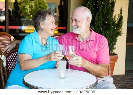 Senior couple on a romantic date, having cocktails at a restauraunt.